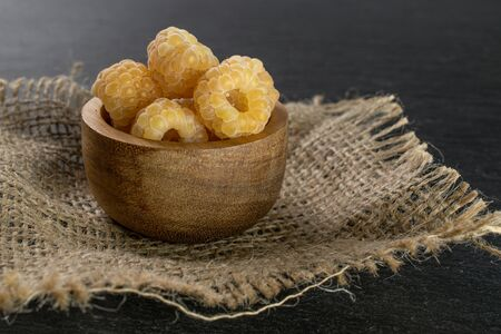 Lot of whole fresh golden hymalayan raspberry in wooden bowl on jute cloth on grey stone