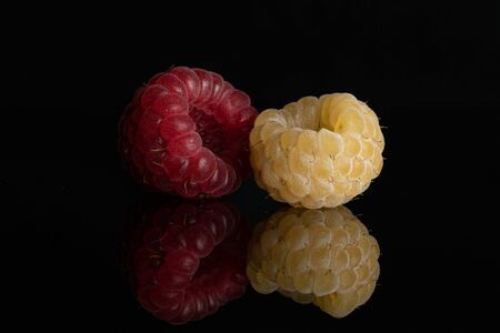 One whole ripe fresh golden hymalayan raspberry with one red berry isolated on black glass Stok Fotoğraf