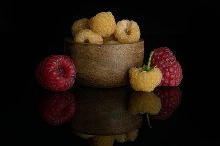 Lot of whole fresh golden hymalayan raspberry with two red berries in wooden bowl isolated on black glass