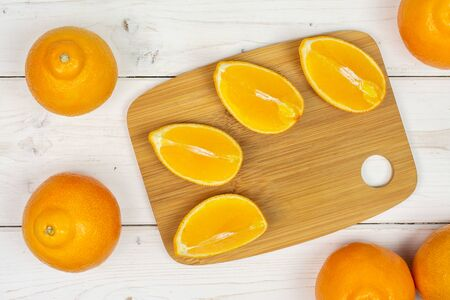 Group of five whole four quarters of fresh orange tangelo minneola on bamboo cutting board flatlay on white wood