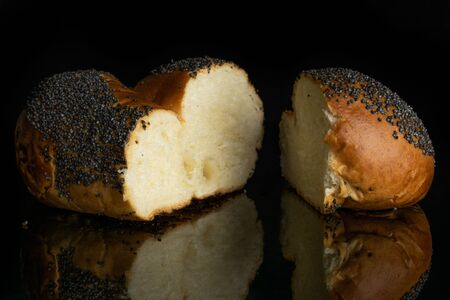 Group of two halves of fresh twisted poppy seed bun isolated on black glass