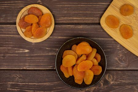 Lot of whole dried orange apricot on round bamboo coaster on bamboo cutting board in dark ceramic bowl flatlay on brown wood