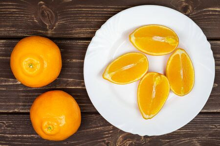 Group of two whole four quarters of fresh orange tangelo minneola on white ceramic plate flatlay on brown wood Banque d'images - 129474029