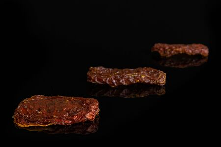 Group of three whole dried red tomato isolated on black glass