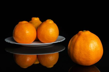 Group of four whole fresh orange tangelo minneola on white ceramic plate isolated on black glass Banque d'images - 129473878