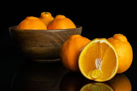 Group of five whole one half of fresh orange tangelo minneola in big wooden bowl isolated on black glass