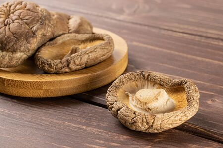 Lot of whole dry mushroom shiitake on bamboo plate on brown wood