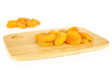 Lot of whole dried orange apricot on bamboo cutting board isolated on white background