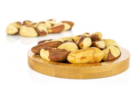 Lot of whole raw brown brazil nut on bamboo coaster isolated on white background 写真素材