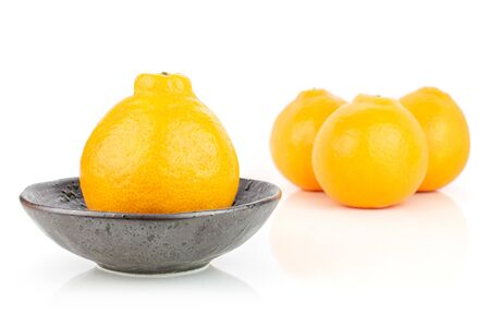 Group of four whole fresh orange tangelo minneola in dark ceramic bowl isolated on white background Banque d'images - 129474421