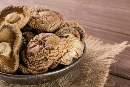 Closeup of lot of whole dry mushroom shiitake on grey ceramic plate on jute cloth on brown wood