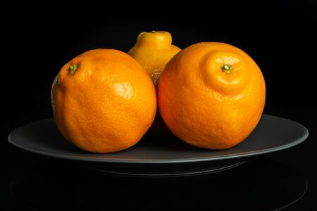 Group of three whole fresh orange tangelo minneola on gray ceramic plate isolated on black glass Banque d'images - 129474339