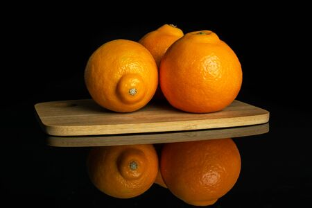 Group of three whole fresh orange tangelo minneola on bamboo cutting board isolated on black glass