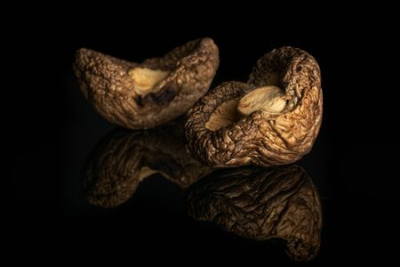 Group of two whole brown dry mushroom shiitake isolated on black glass Reklamní fotografie
