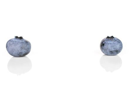 Group of two whole fresh blue bilberry isolated on white background