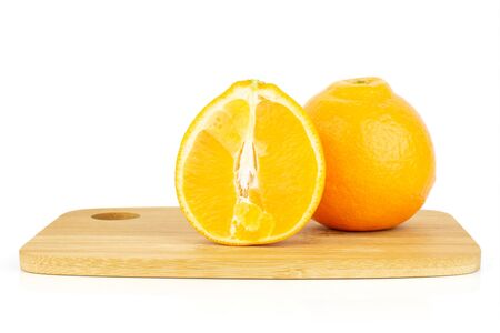 Group of one whole one half of fresh orange tangelo minneola on bamboo cutting board isolated on white background Banque d'images - 129474138