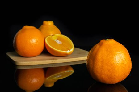 Group of three whole one half of fresh orange tangelo minneola on bamboo cutting board isolated on black glass Banque d'images - 129474614