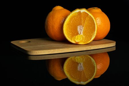 Group of two whole one half of fresh orange tangelo minneola on bamboo cutting board isolated on black glass Banque d'images - 129474621