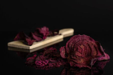 Lot of slices of dried red beetroot few are in the front and the rest is on small wooden cutting board isolated on black glass