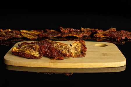 Lot of whole dried red tomato on bamboo cutting board isolated on black glass