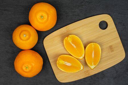 Group of three whole three quarters of fresh orange tangelo minneola on bamboo cutting board flatlay on grey stone