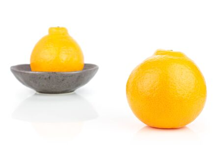 Group of two whole fresh orange tangelo minneola in dark ceramic bowl isolated on white background Banque d'images - 129474402