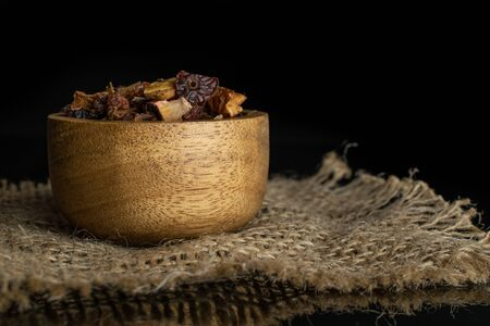 Lot of pieces of lingonberry strawberry fruit tea in wooden bowl on jute cloth isolated on black glass