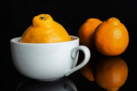 Group of three whole fresh orange tangelo minneola in white ceramic cup isolated on black glass Banque d'images - 129474630