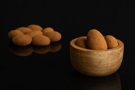 Lot of whole sweet brown chocolate cinnamon almond in tiny wooden bowl isolated on black glass