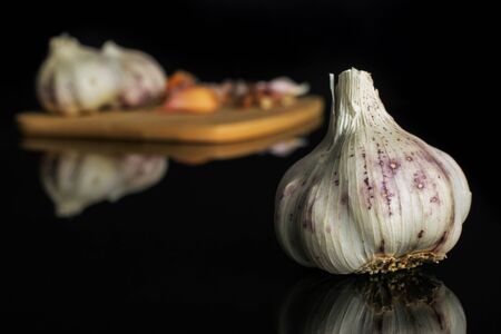 Group of three whole lot of pieces of organic white garlic allium sativum on bamboo cutting board isolated on black glass