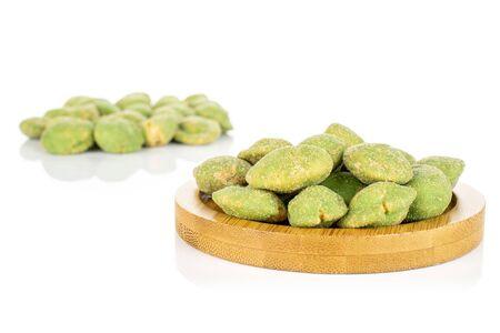 Lot of whole spicy green wasabi peanut small group is in the back and the rest is on bamboo coaster isolated on white background