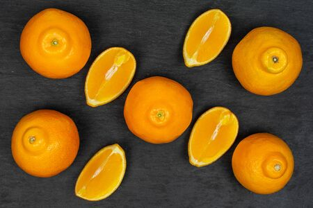 Group of five whole four quarters of fresh orange tangelo minneola flatlay on grey stone Banque d'images - 129474810