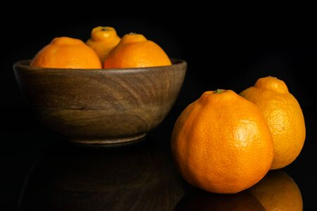 Group of five whole fresh orange tangelo minneola in big wooden bowl isolated on black glass