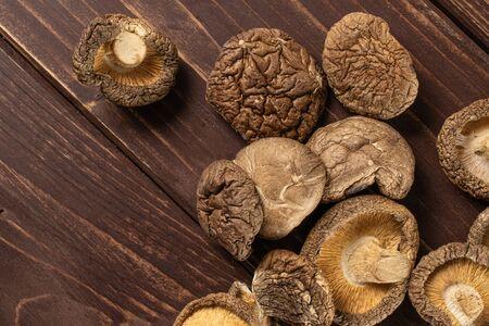 Lot of whole dry mushroom shiitake flatlay on brown wood