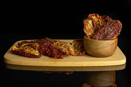 Lot of whole dried red tomato in tiny wooden bowl on bamboo cutting board isolated on black glass