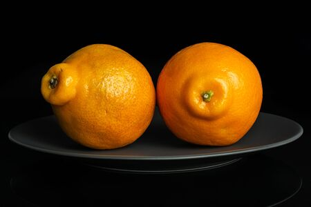 Group of two whole fresh orange tangelo minneola on gray ceramic plate isolated on black glass Banque d'images - 129474867