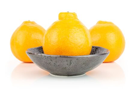 Group of three whole fresh orange tangelo minneola in dark ceramic bowl isolated on white background Banque d'images - 129474953