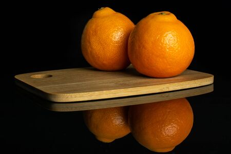 Group of two whole fresh orange tangelo minneola on bamboo cutting board isolated on black glass