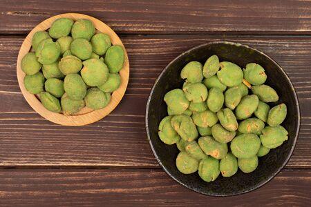 Lot of whole spicy green wasabi peanut on bamboo coaster in dark ceramic bowl flatlay on brown wood Stockfoto