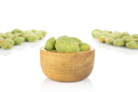 Lot of whole spicy green wasabi peanut two groups are in the back and the rest is in tiny wooden bowl isolated on white background