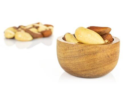 Lot of whole raw brown brazil nut in tiny wooden bowl isolated on white background 写真素材