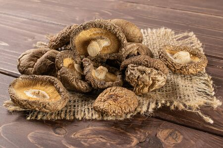 Lot of whole dry mushroom shiitake on jute cloth on brown wood