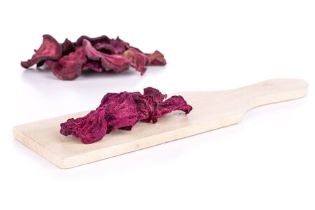 Lot of slices of dried red beetroot on small wooden cutting board isolated on white background
