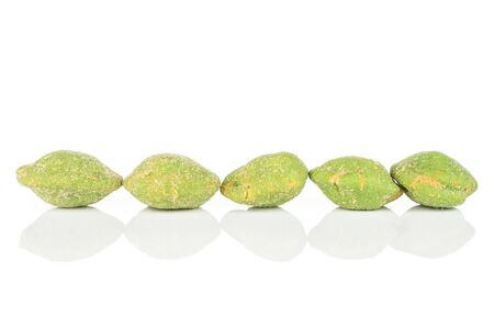 Group of five whole spicy green wasabi peanut isolated on white background