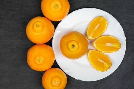 Group of five whole three quarters of fresh orange tangelo minneola on white ceramic plate flatlay on grey stone Banque d'images - 129475115