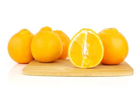 Group of four whole one half of fresh orange tangelo minneola on bamboo cutting board isolated on white background