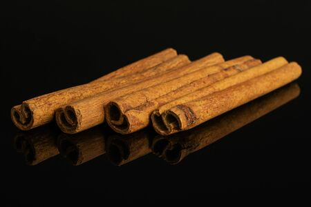 Group of four whole dry brown cinnamon isolated on black glass 免版税图像