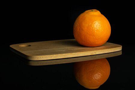 One whole fresh orange tangelo minneola on bamboo cutting board isolated on black glass Stock fotó