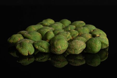 Lot of whole spicy green wasabi peanut in a large group isolated on black glass