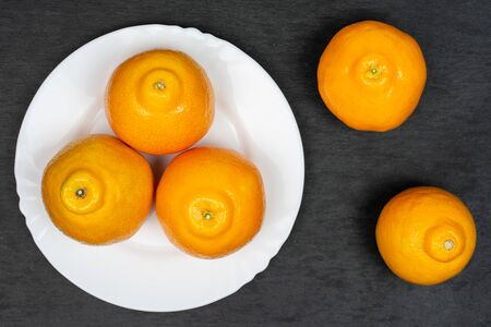Group of five whole fresh orange tangelo minneola on white ceramic plate flatlay on grey stone Banque d'images - 129475195